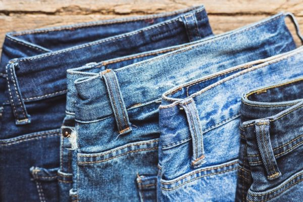jeans-stacked-on-a-wooden-background-P3UEQU7
